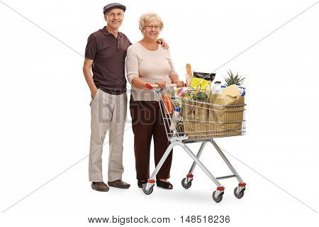 Full length portrait of an elderly couple posing with a shopping cart full of groceries isolated on white background