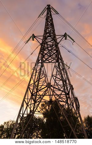 Metal power line against the pink sunset sky