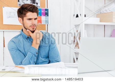 Close up portrait of a thoughtful young casual businessman sitting at the desk and using laptop at the office