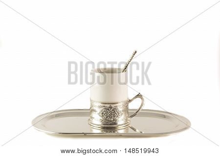 One white porcelain coffee Cup with silver spoon on a tray on a white background