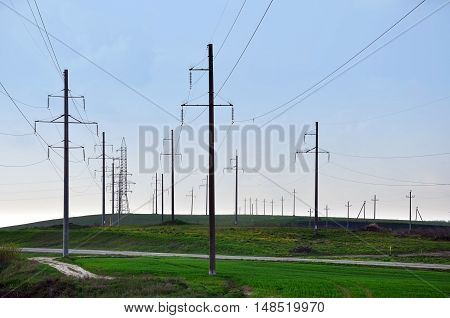 Many power line towers and wires on a background of grass and blue sky in perspective.