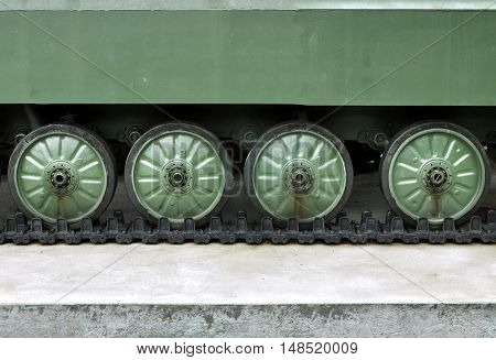 Background on the military theme. Chassis tank standing on the ground. Front view of crawler. Place for an inscription.