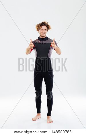 Full length portrait of a happy joyful sportsman in diving suit showing thumbs up over white background