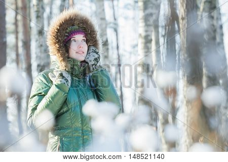 Young attractive woman is holding woolly mittens near her head in winter forest outdoors