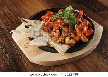 Fajitas with chicken and bell pepper in a pan. Wooden background.
