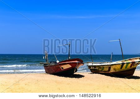 Two fishing boats on the beach by the ocean on the background of yellow sand and blue sky