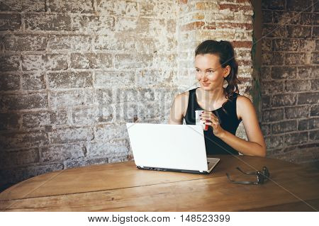 Beautiful young female is sitting in a coffee house and using laptop computer, drinking cafe, looking at left side. Brick is wall on the background