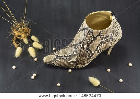 Shoes snakeskin with pearls and spikes on a dark background.