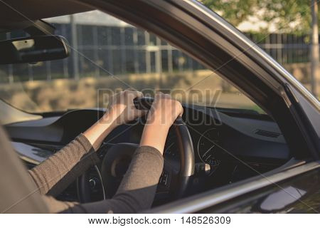 A woman driving a modern car during day light