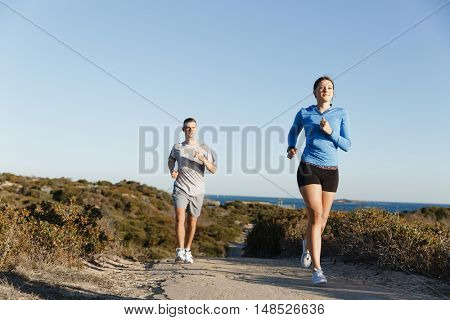 Sport runner jogging on beach working out with her partner