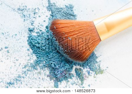 Blank background with crumbly blue eye shadows and brush