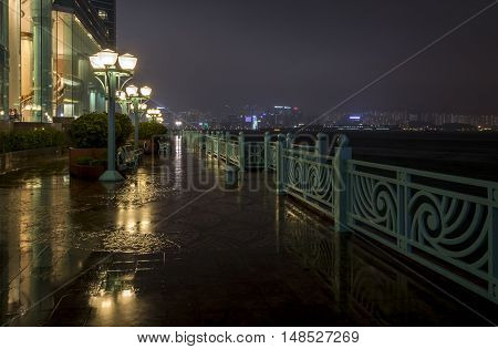 Wet harbor side walkway lined with lamps and benches at night