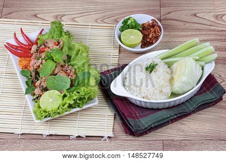 Sticky rice with spicy sour mixed herb salad of chicken and liver pork . Side view.
