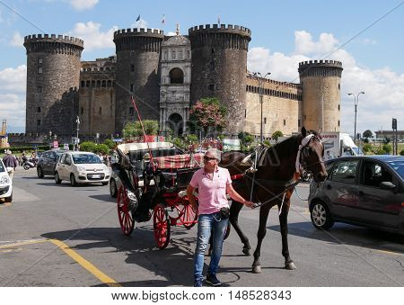 Naples Italy September 2016: horse carriage for tourists near the medieval castle of Maschio Angioino or Castel Nuovo (New Castle) Naples Italy