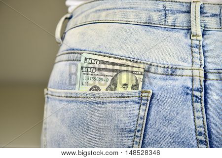 Money sticking out of a blue jean pocket.