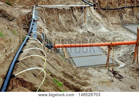The process of lowering the groundwater level. Industrial sand quarry with water and a metal tube around it with thin tubes directed at the ground.
