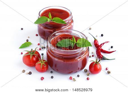 Tomato sauce and basil in glass jars on a white background