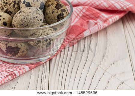 Quail eggs in a glass bowl on old white wooden table. Selective focus.