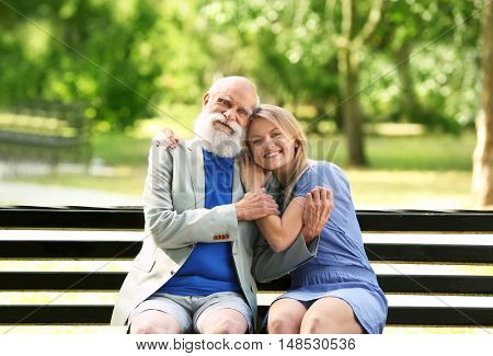 Grandfather and granddaughter sitting on a bench
