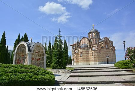 The Hercegovacka Gracanica Monastery on Crkvina Hill above Trebinje in Bosnia. The monastery was built in 2000 and is an exact copy of the Gracanica Monastery in Kosovo. A small water fountain with taps can be seen on the left.