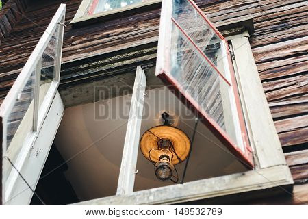 Old grunge lamp with wide lampshade and gleaming glass bulb in window