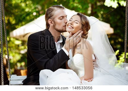 Young beautiful newlyweds smiling, kissing, sitting on swing in park. Copy space.