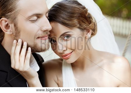 Happy beautiful newlyweds in suit and wedding dress smiling, enjoying. Copy space.