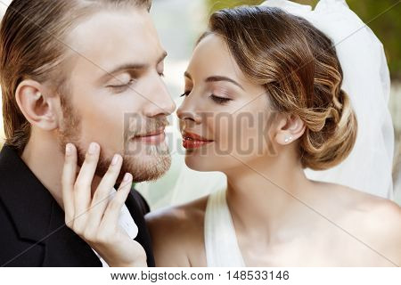Young beautiful newlyweds smiling with closed eyes, enjoying. Copy space.