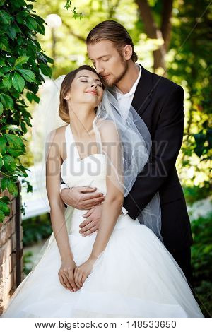 Happy newlyweds smiling with closed eyes, embracing in park. Copy space.