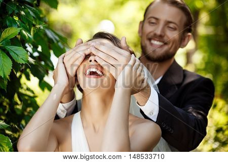 Couple of happy newlyweds smiling. Groom covering bride's eyes with hands. Copy space.