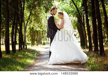 Young beautiful dressy newlyweds smiling, posing, embracing in park. Copy space.