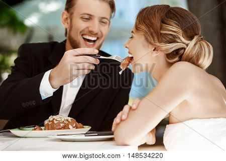 Young handsome groom feeding his beautiful blonde bride with croissant in cafe. Copy space.