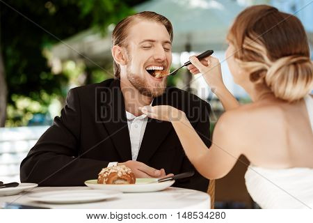 Young beautiful blonde bride feeding her groom with croissant in cafe. Copy space.