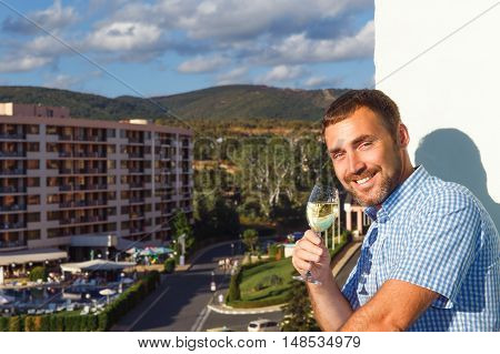 handsome guy standing on balcony in luxury hotel in Bulgaria at sunset and drinking white wine.