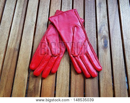 Red womens leather gloves on wooden boards