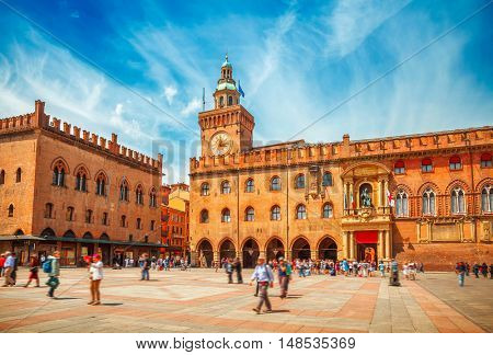 Italy Piazza Maggiore in Bologna old town tower of hall with big clock and blue sky on background. Antique buildings terracotta galleries
