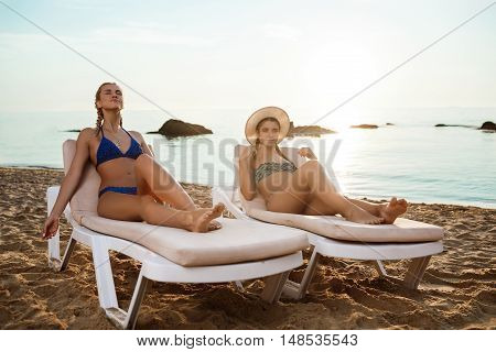 Young beautiful girls in swimwear sunbathing, lying on chaises near sea. Copy space.