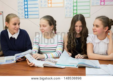 Four young girls are sitting at the wooden table with opened textbooks.