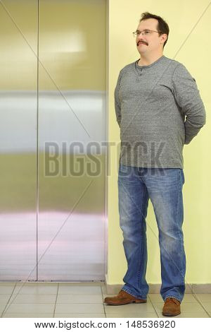The man in glasses with a mustache standing near close elevator doors