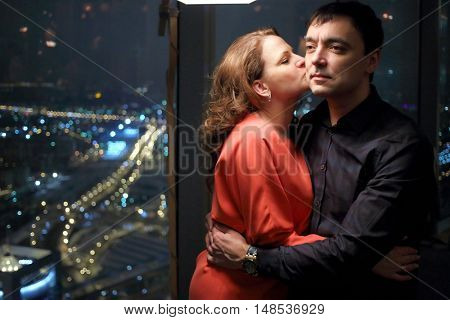 A woman in a red dress is kissing a man standing near a big window with a view of the city in a restaurant in the evening