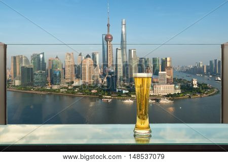 Beer and foam beer on table in rooftop bar with Shanghai skyscraper in background in Shanghai China. Viewpoint of Shanghai China.