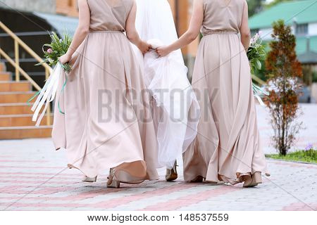 Beautiful bride and bridesmaids walking to church