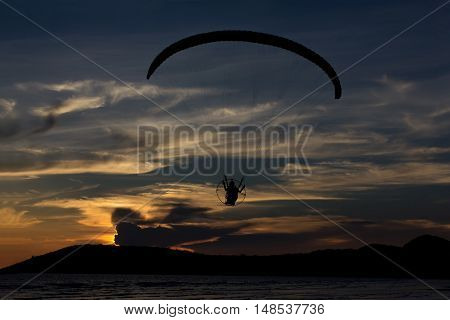 Silhouette paramotor / paraglider flying on the sky with seaview