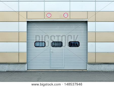 Facade of a modern building made of sandwich panels with folded garage doors and marks the height restrictions. Front view.