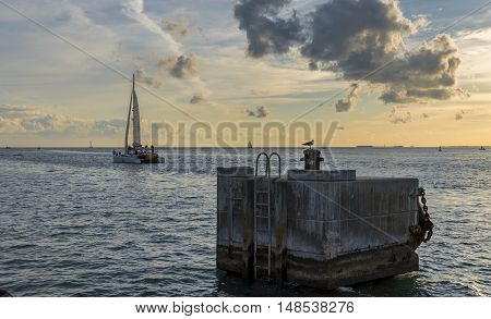 Catamaran, sailing towards the horizon, with a concrete dock in the foreground