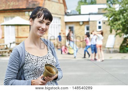 Portrait Of Teacher With Bell Supervising Break In School Playground
