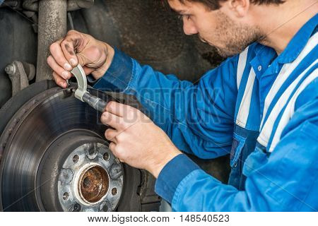Young male car mechanic examining brake disc with caliper in automobile shop