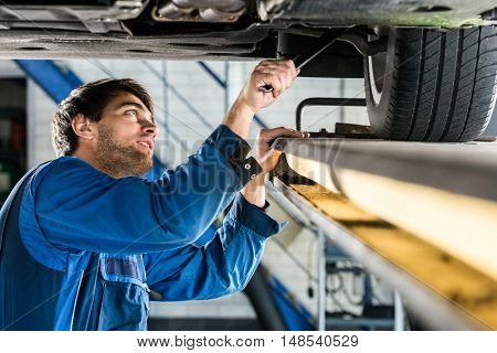 Young male mechanic changing tire from suspended car at automobile shop