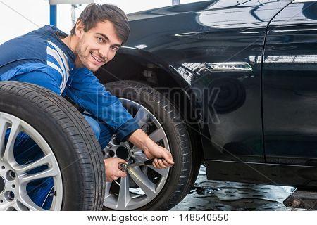 Portrait of confident male mechanic changing car tire at automobile shop