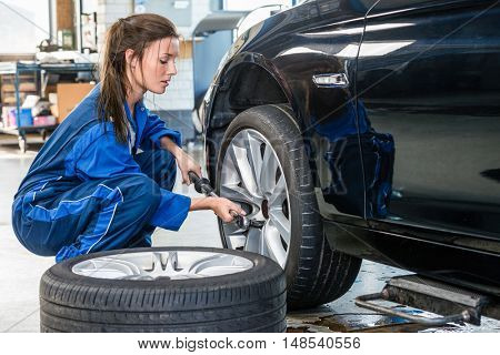 Young female mechanic changing car tire at automobile shop